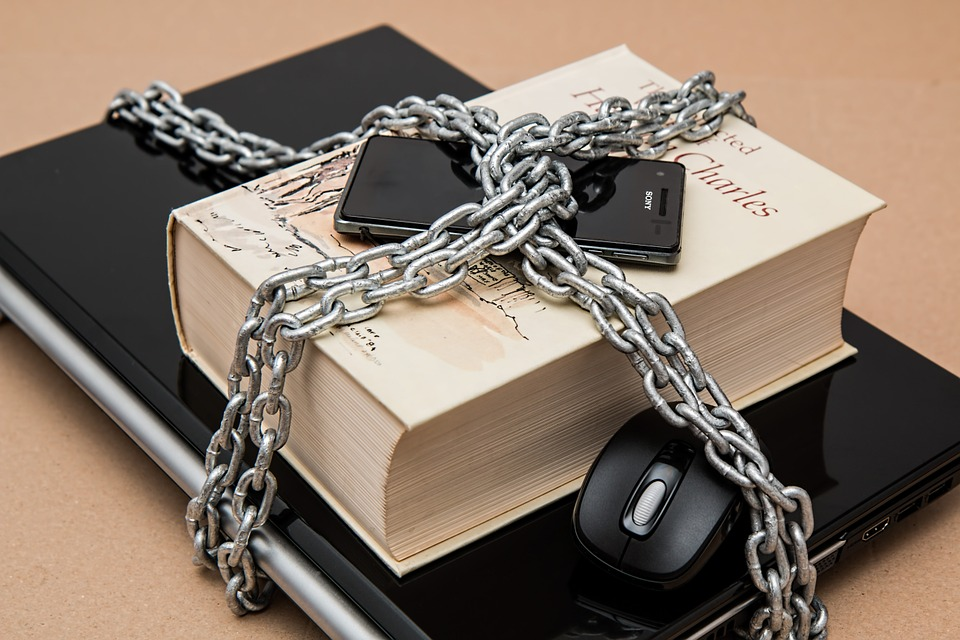 Photo showing a laptop, a book and a smartphone chained under lock and key. Censorship.