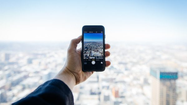 Phone in the hand of a person overlooking a city